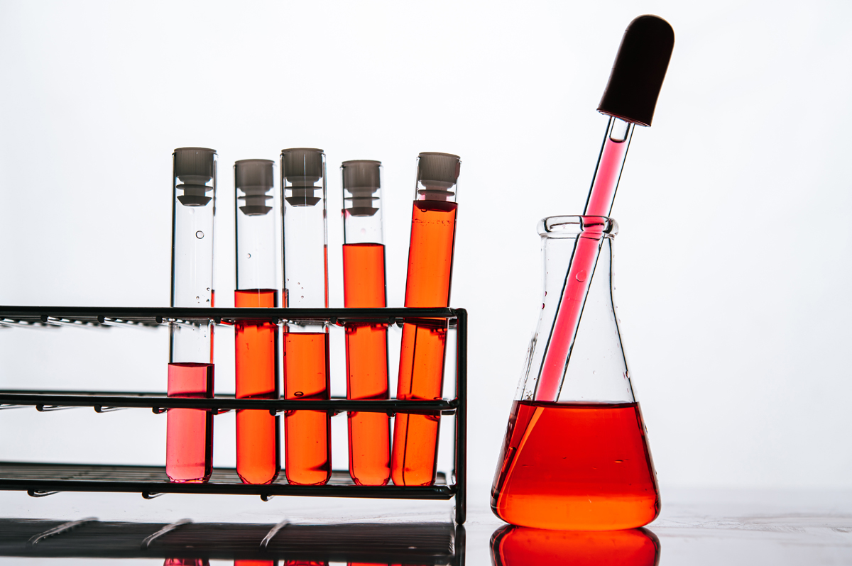 Orange chemicals in a science glass tube arranged on a shelf.
